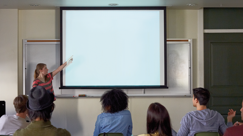 Woman presenting at a white board in front of people.