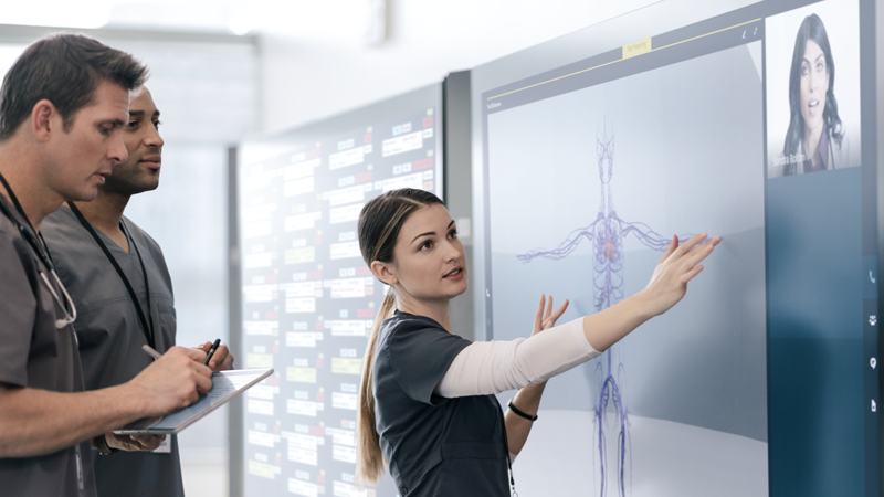 Woman touching a digital whiteboard with men in medical clothing taking notes