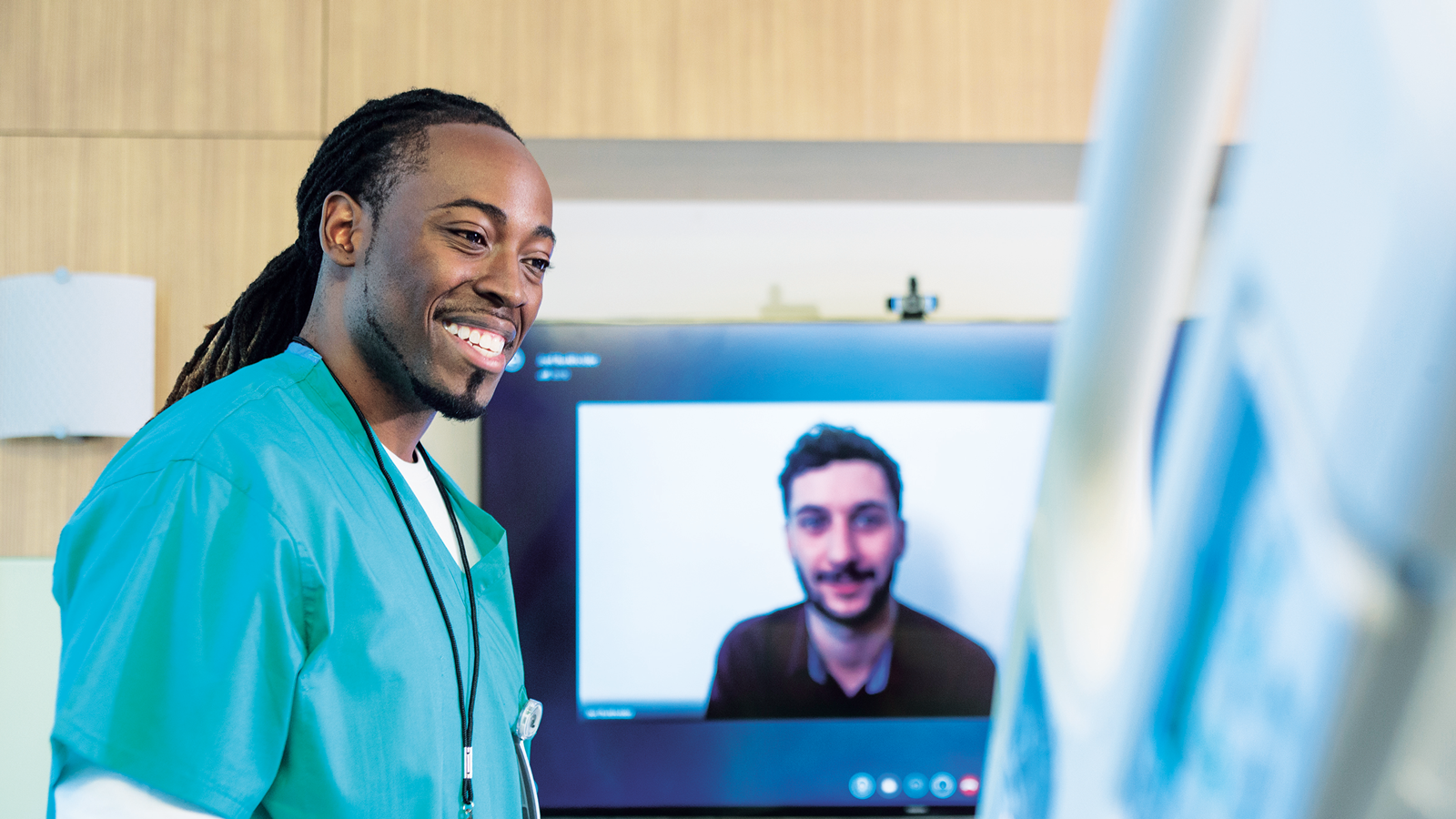 Man in green scrubs with Skype in the background