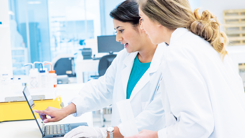 Two women in medical coats looking at a laptop